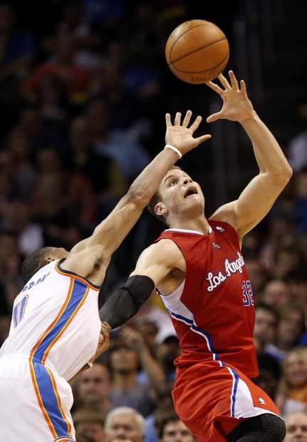 Clippers power forward hauls in a pass over the outstretched arm of Thunder point guard Russell Westbrook in the second half Wednesday night in Oklahoma City.