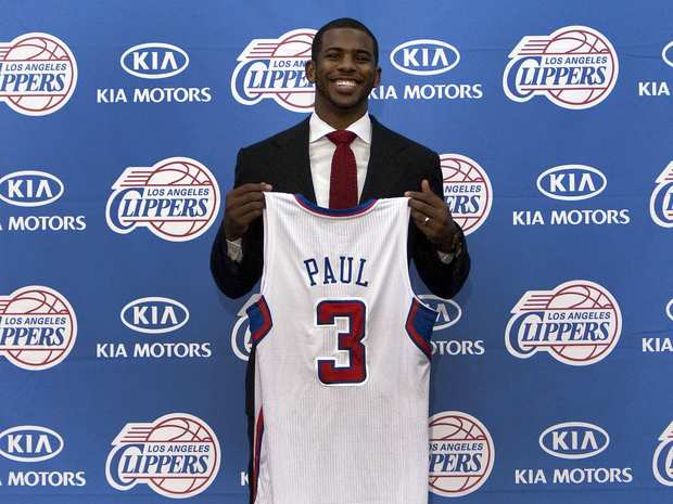 Clippers point guard Chris Paul poses with his new team jersey during a team news conference on Thursday.