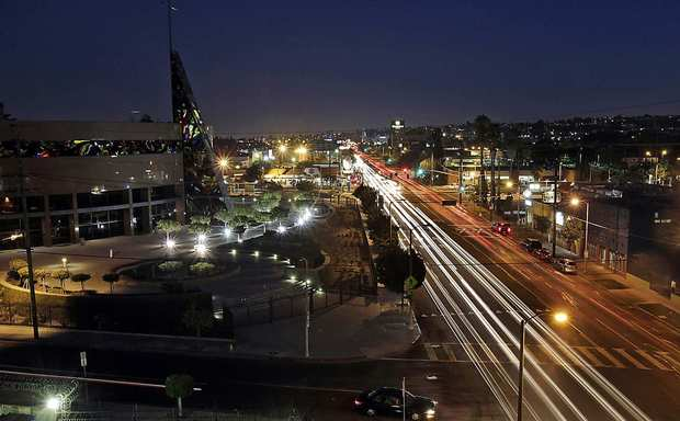 Traffic streams along Crenshaw Boulevard near its intersection with Exposition Boulevard in the Crenshaw district of Los Angeles. The district is about 60% African American. Prominent buildings along this stretch of the boulevard include the West Angeles Cathedral, left, the Baldwin Hills Crenshaw Plaza shopping center and the Angelus Funeral Home, which was designed by noted architect Paul R. Williams.