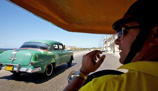 "An old American car passes a ""coco cab"" taxi along Havana's famous seaside Malecon, the palm-lined boulevard that stretches the length of the city."