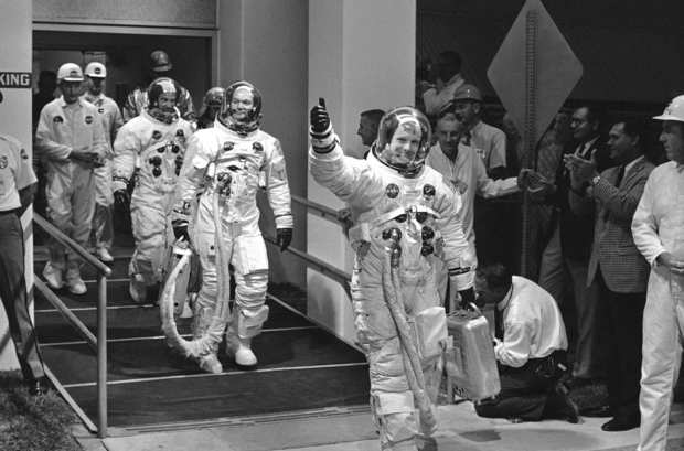 "Apollo 11 astronauts, from right, Neil Armstrong, Michael Collins and Edwin A. ""Buzz"" Aldrin Jr. appeared in a cheerful mood as they left the Manned Spacecraft Operations Building to enter the transfer van that takes them to Pad 39 to enter the Command Module on July 16, 1969, at Cape Kennedy, Fla."