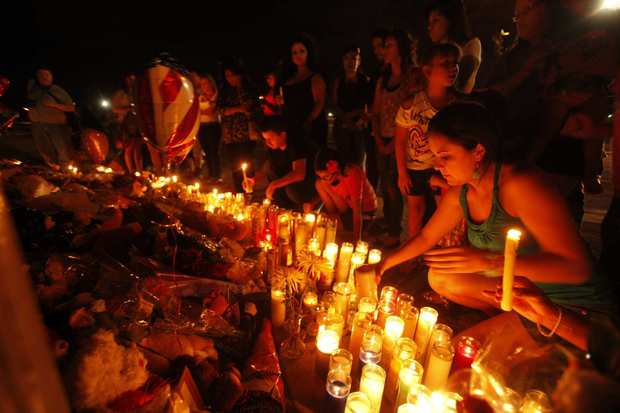 People light candles at the roadside memorial.