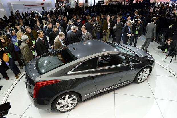 Members of the media view the Cadillac ELR coupe vehicle after the unveiling.