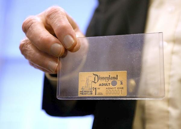 Disney archivist Dave Smith holds the first Disneyland admission ticket ever sold. The ticket was purchased by Roy O. Disney.