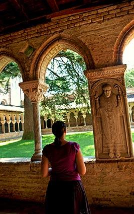 A visitor admires the stone work in the Romanesque cloister of the Abbey of St.-Pierre in Moissac, France. The 12th century Benedictine abbey and church boast one of the most outstanding carved walls, called tympanum, of Romanesque art.
