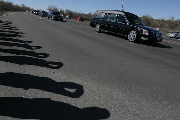 A hearse carrying the body of slain Riverside Police Officer Michael Crain passes by a detail of saluting law enforcement officers from Orange and Riverside counties during his funeral procession along Van Buren Boulevard en route to the Riverside National Cemetery.