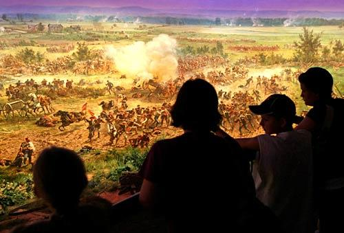 Visitors watch and listen as lighting and sound bring the battle to life inside the park's cyclorama theater. The massive painting depicts the ill-fated Confederate charge led by Gen. George Pickett. In its 19th century heyday, it reportedly brought veterans to tears.
