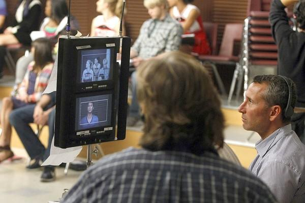 "Director Adam Shankman, right, watches as the ""Glee"" cast is framed in the shot."