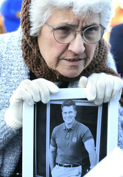 Mary Cardona holds a photo of Huell Howser as she and hundreds of others gather to celebrate and remember the life of television host Huell Howser during a memorial tribute at Griffith Observatory on Tuesday. 