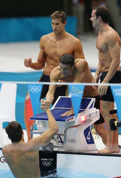 Michael Phelps reaches into the pool to congratulate teammate Nathan Adrian who swam the last leg of the men's 4x100 medley relay to win the gold medal. Matt Grevers and Brendan Hansen also swam in the relay.