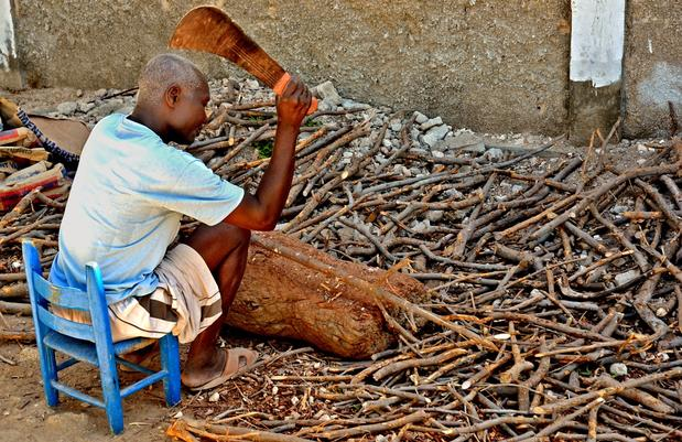 A man chops kindling outside a church in Gonaives.