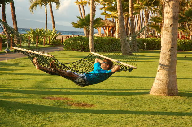 A traveler unwinds in a hammock along the Kaanapali Beachwalk, Maui.