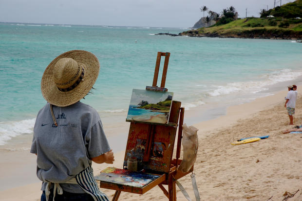 An artist does his best to capture the blue hues of the Pacific along the North Shore of the island.