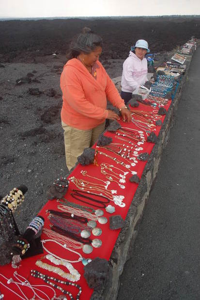 Roadside merchants stand out boldly amid the miles of hardened black lava along the island's west coast.