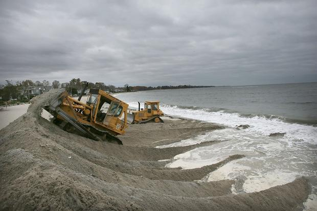 Earthmovers build protective berms on Compo Beach as the first signs of Hurricane Sandy approach in Westport, Conn.
