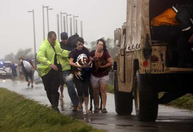 Rescuers help people in Braithwaite, La., where dozens were stranded by floodwaters.