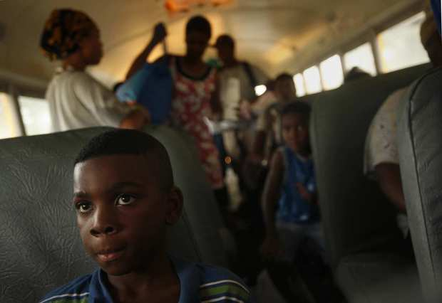Nine-year-old Reshard Johnson and other residents of Kentwood, La., ride buses to a shelter away from a possible dam break along the Tangipahoa River. (Carolyn Cole/Los Angeles Times)