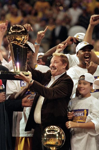 Jerry Buss holds aloft the NBA championship trophy after the Lakers defeated the Indiana Pacers for the 1999-2000 title, the franchise's first since the Showtime Era in the 1980s.