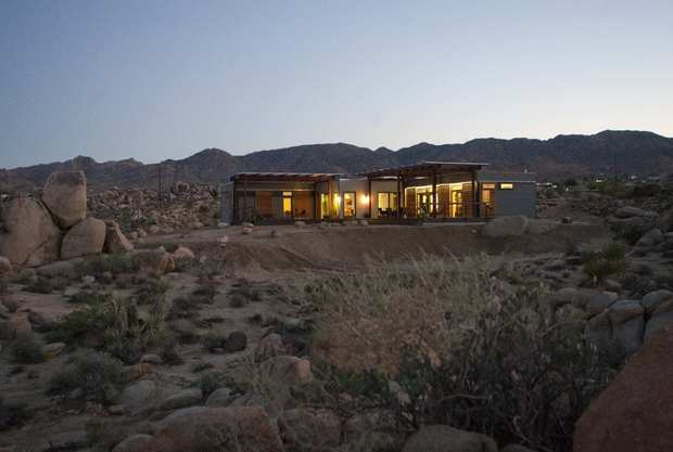 The low-slung prefab house built for Tim Disney by Blu Homes sits in the otherworldly landscape of Joshua Tree. The indoor-outdoor design, pictured here from the rear, includes generous shaded decks and a detached guest house, out of view here. Its prefab modules were built in less than eight weeks in a factory, then transported by truck and craned into place.