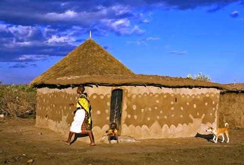 A Masai woman in a traditional <i>boma</i>, or village. This is a classic Masai dwelling.