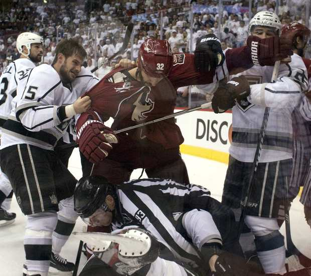 Kings forwards Brad Richardson and Jarret Stoll hold back Coyotes defenseman Michael Stone as a referee tries to break up a fight during Game 2 on Tuesday night at Jobing.com Arena.