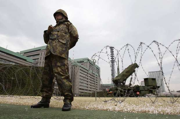 A member of the Japan Self-Defense Forces stands near a PAC-3 Patriot missile unit deployed for North Korea's rocket launch.