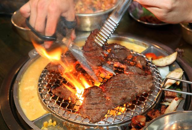 Portions of galbi beef are cut into smaller pieces as it cooks on a tabletop burner. Beaten egg and corn with cheese are also arrayed around the burners.