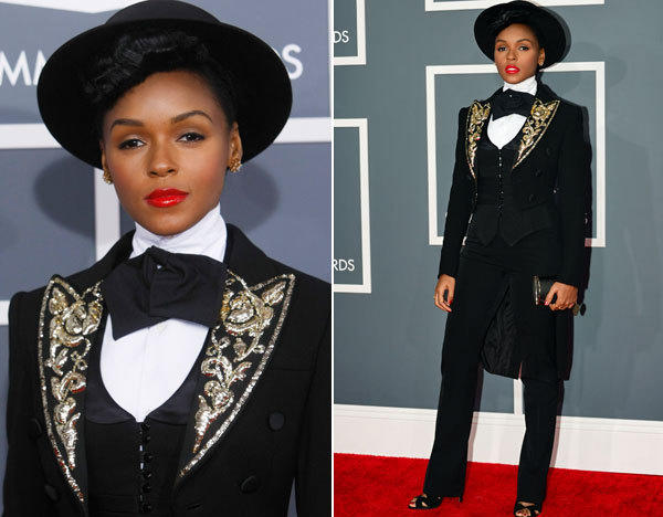 "Janelle Monae worked her signature androgynous look in a tux jacket with sparkly lapels, a dripping bow tie and a flat top hat. She told E!, ""I'm wearing ideas,"" and credited her stylist Erin Hirsh for putting it all together."