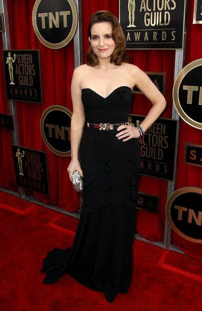 There is a lot of dark blue and black on the carpet. Tina Fey looks as good as she ever has in a strapless black Oscar de la Renta gown with a sparkly belt.