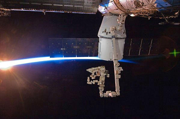 The SpaceX Dragon cargo vessel berthed to the International Space Station, with rays of sunshine and the Earth's atmosphere in the background.