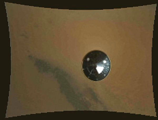 An image taken as the Curiosity rover descended toward Mars shows its separated 150-foot-diameter heat shield about 50 feet from the spacecraft.