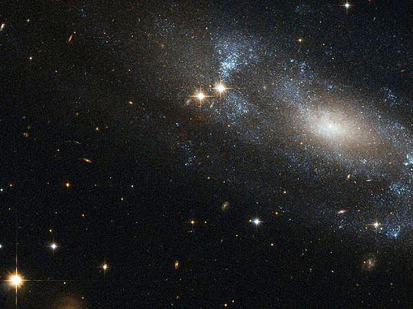 An image from the Hubble Space Telescope shows the spiral galaxy ESO 499-G37 against a backdrop of distant galaxies and nearby stars.