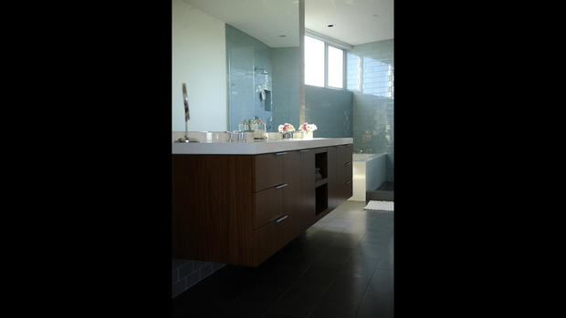 "In the master bathroom, designer and builder Noah Walker installed blue and gray glass tile. The large mirror and windows make the bathroom feel significantly larger. ""There's never too much light for me,"" homeowner Tiffany Chen said. ""We don't have to turn on the lights until it gets dark outside."" [ <a href=""http://www.latimes.com/features/home/la-lh-manhattan-beach-noah-walker-house-photos,0,710950.photogallery""><FONT COLOR=""#2262cc"">Full gallery</FONT></a> ]"