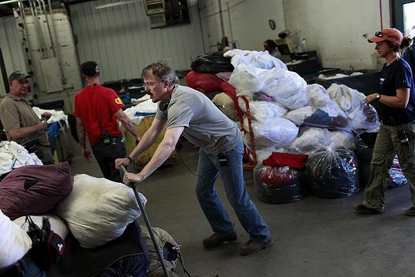 "Director and ""Breaking Bad"" show runner Vince Gilligan, center, helps move props before shooting on location inside an industrial laundry facility in Albuquerque. Gilligan, who created the show, is an executive producer and occasionally directs."