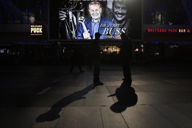 Lakers fans Mitchell Veintemilla, left, and Angel Delgado check their phones as they try to get tickets to the game against the Celtics on Wednesday night. They're standing in front of a giant screen paying tribute to late Lakers owner Jerry Buss in Nokia Plaza.
