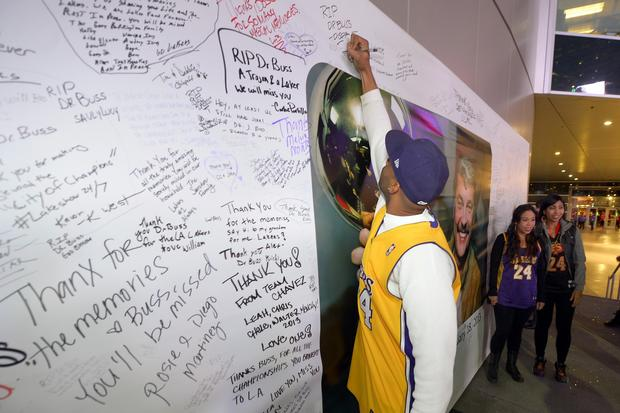 Tarron Steward finds space above the photo of late Lakers owner Jerry Buss on which to write a message Wednesday night before the Lakers-Celtics game at Staples Center.