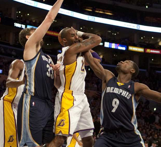 Lakers guard Kobe Bryant gets tangled with Grizzlies center Marc Gasol and guard Tony Allen while trying to drive to the basket in the first half Sunday at Staples Center.