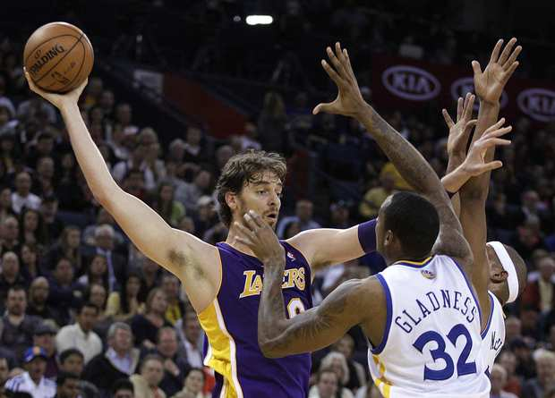 Lakers power forward Pau Gasol fends off Warriors center Mickell Gladness and forward Dominic McGuire while protecting the ball and looking to pass in the first half Wednesday night in Oakland.