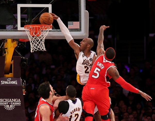 Lakers guard Kobe Bryant dunks as Hawks forward Josh Smith attempts to block him.