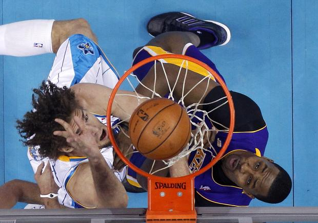 Lakers center Dwight Howard challenges a shot by Hornets center Robin Lopez in the first half Wednesday night.