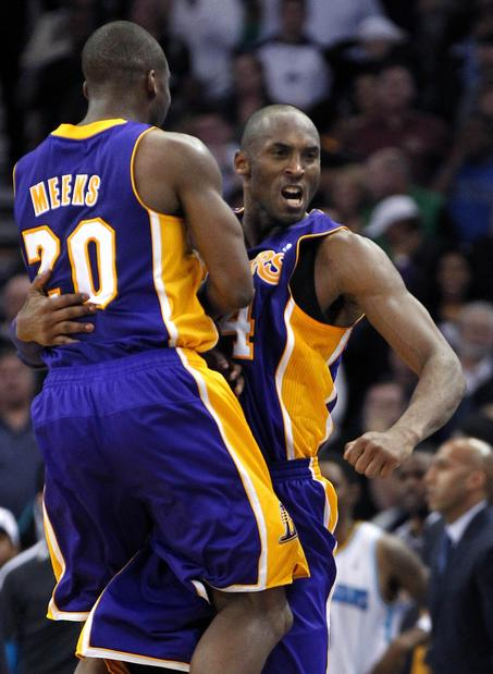 Lakers guard Kobe Bryant celebrates with teammate Jodie Meeks after his breakaway dunk against the New Orleans Hornets.