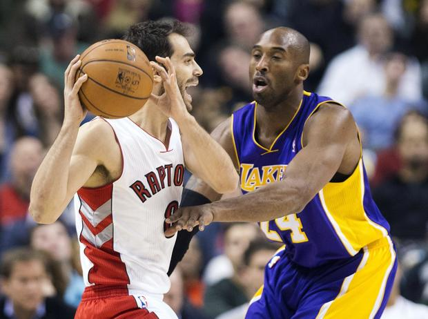 Lakers guard Kobe Bryant tries to knock the ball from the grasp of Raptors guard Jose Calderon in the first half Sunday.