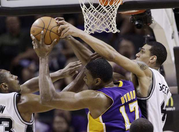 Lakers center Andrew Bynum tries to collect a rebound against Spurs forward Boris Diaw and guard Danny Green in the second half Wednesday night in San Antonio.