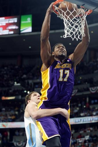 Nuggets center Timofey Mozgov can't prevent Lakers center Andrew Bynum from scoring despite clutching him around the waist during the first half of Game 4 on Sunday night in Denver.