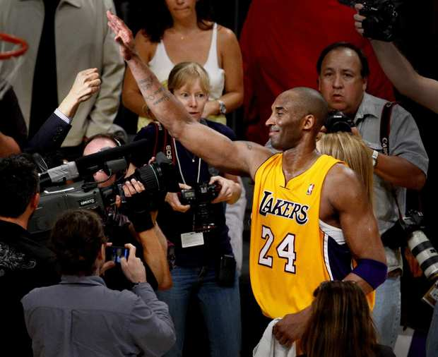 Guard Kobe Bryant gets a high-five from a fan after the Lakers defeated the Nuggets, 96-87, in Game 7 of their first-round playoff series on Saturday night at Staples Center.