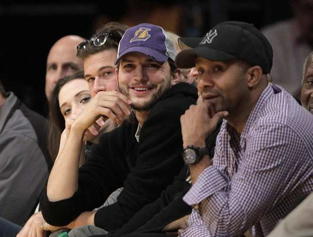 Ashton Kutcher, center, watches an NBA basketball game between the Lakers and the Houston Rockets.