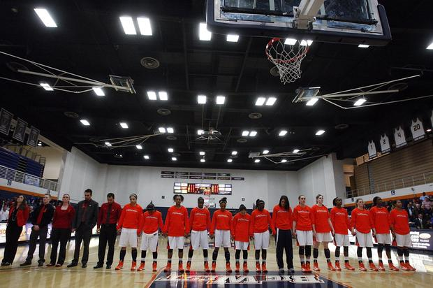 Members of the Cal State Fullerton women's basketball team join hands for a moment of silence to honor slain assistant coach Monica Quan before a home game against UC Irvine.