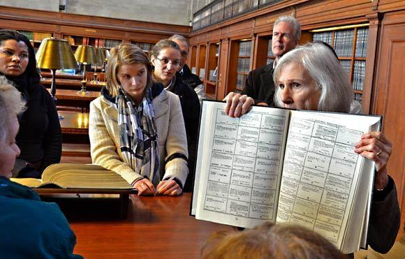 Docent Julie Chelminski leads visitors through the old catalog room of the New York Public Library's 100-year-old Schwarzman Building at Fifth Avenue and 42nd Street. She holds a book that shows what the cards in the old card catalog looked like.