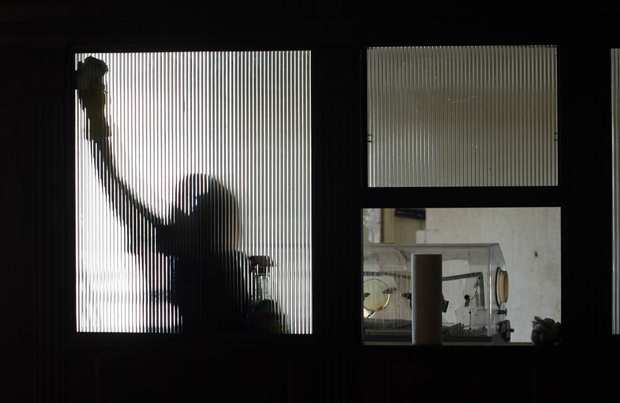 A maintenance worker cleans a window inside the former Linda Vista Community Hospital in Boyle Heights. The site, which some say is haunted, is set to be converted into apartments for low-income seniors. The incubator at right is left over from a film shoot.