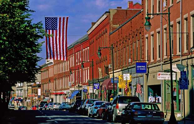 Vintage buildings and American flags line Main Street in Rockland, Maine. Mid-coast Maine boasts many such picturesque towns where the rhythm of life slows down to an agreeable pace.